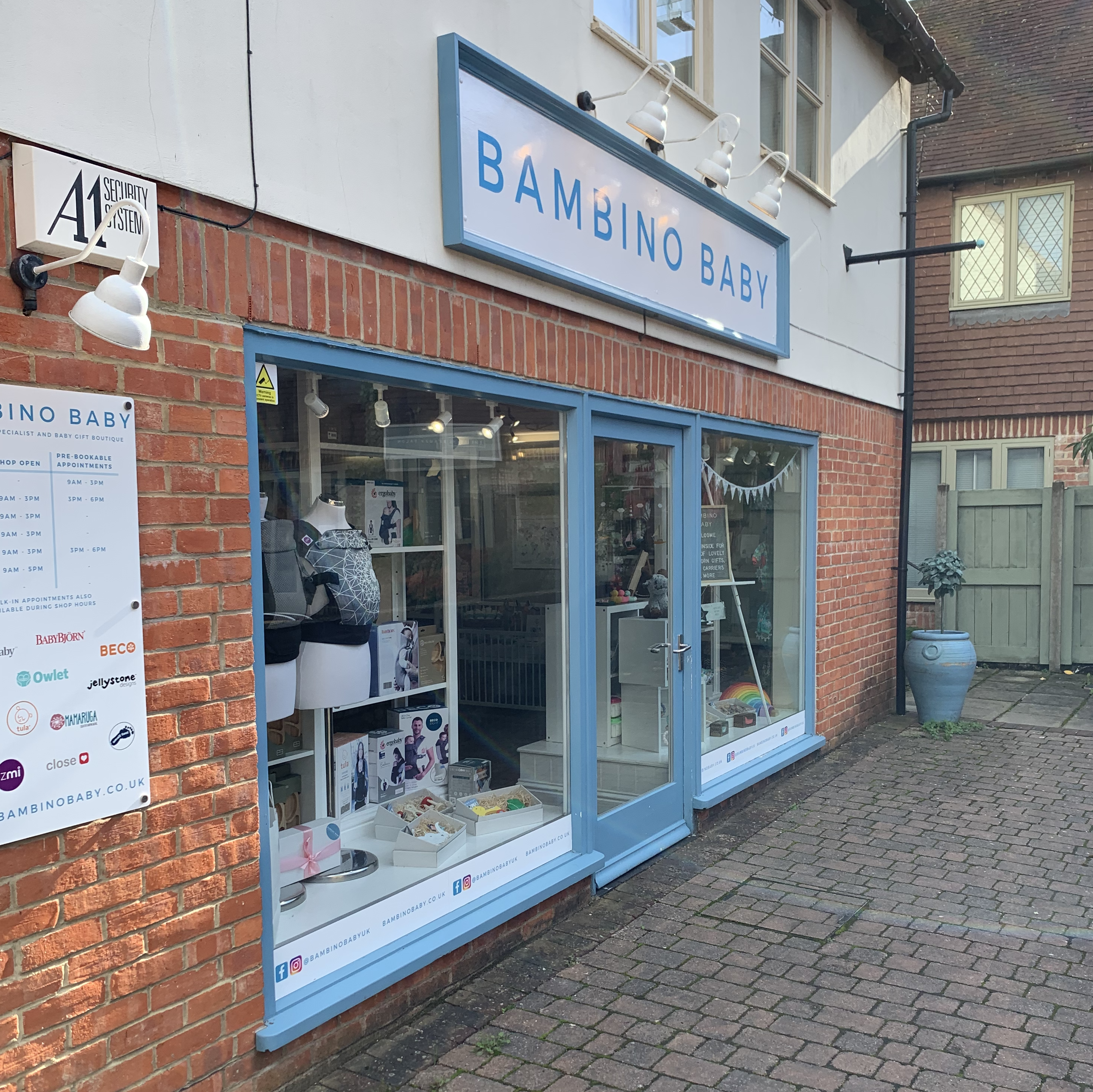 Shop front with two large glass windows, displaying baby carriers and gifts, with Bambino Baby sign above